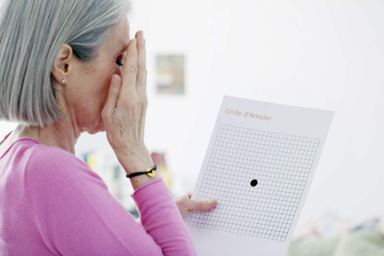 A 50 to 60 year old woman testing her vision with an macular degeneration grid